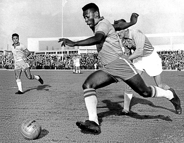Pelé dribbling past a defender